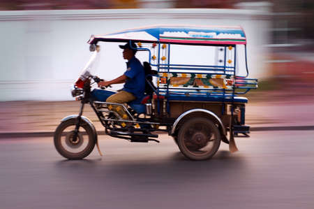 TukTuk speeds past in Vientiane, Laos  photo