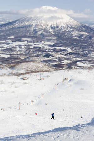 piste: Wide view of the ski slopes on Mount Niseko Annupuri in the ski resort of Niseko with Mt Yotei in the background Editorial