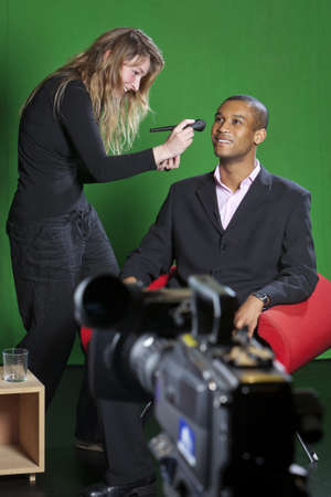 adds: Description A make-up artist adds final touches to a presenter on a television set with a TV camera out of focus in the foreground