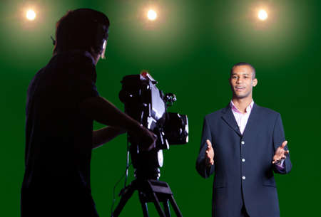 video camera: Presenter talking to camera in a green screen studio with silhouetted cameraman in foreground and studio lights in the background