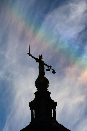 Lady Justice atop the Old Bailey in London, silhouetted against a vibrant blue sky with a faint rainbow