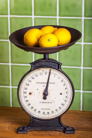Old mechanical kitchen scales with lemons in the pan photo