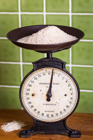 Old mechanical kitchen scales with rice in the pan