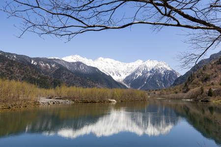 꼭대기가 눈으로 덮인: Snow-capped Hotaka mountain range reflected in Taisho Pond in the Kamikochi area of the Japanese Alps 스톡 사진