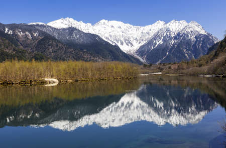 snowcapped: Snow-capped Hotaka mountain range reflected in Taisho Pond in the Kamikochi area of the Japanese Alps  Stock Photo