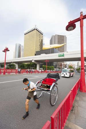 flamme: Tokyo, Japan - May 26, 2012  A man pulls an empty rickshaw across the Azuma bridge in Tokyo