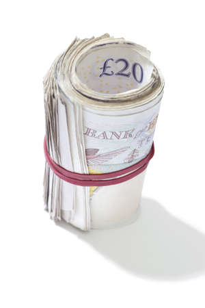 elastic band: A roll of British notes held together by an elastic band on a white background