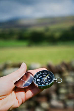 Female hand holds compass up to establish direction