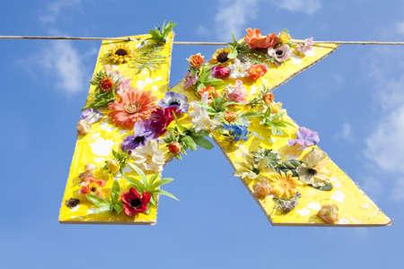 cardboard cutout: Sagoma di cartone della lettera K, dipinto di giallo e coperto di fiori che appendono su una linea contro un cielo blu estate