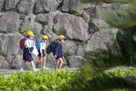 potentially: Sakura-jima, Japan - April 23, 2012  Three schoolchildren walk home wearing hard hats to protect against potentially dangerous debris from Sakura-jima volcano