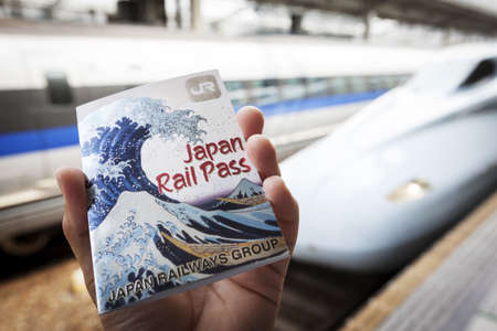 purchased: Okayama, Japan - May 8, 2012  Close-up of a male hand holding a Japan Rail Pass at Okayama train station with Shinkansen trains in the background  The pass can be purchased outside of Japan by foreign travellers to give unlimited train travel for a fixed