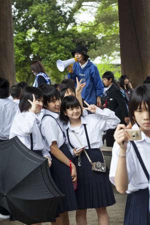 guia turistico: Nara, Jap�n - 09 de mayo 2012 los escolares japoneses posan para una fotograf�a, mientras que en un viaje escolar a Todai-ji templo, habla un gu�a tur�stico a trav�s de un meg�fono ruidosamente en el fondo