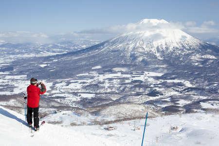 ski slopes: Niseko, Giappone - 4 marzo 2012 Un sciatore prende una fotografia del Monte Yotei dalla cima delle piste da sci di Niseko Annupuri montagna a Niseko, Hokkaido, Giappone