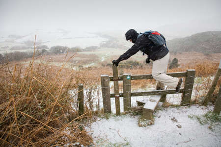 north yorkshire: walker climbs a stile in the snow in Ravenscar, North Yorkshire, England, UK Stock Photo
