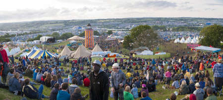 Glastonbury, United Kingdom - June 22, 2011  Panoramic view showing crowds of people on the hill overlooking the site of Glastonbury Festival in 2011  The three day event is the world
