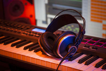 Headphones rest on a MIDI keyboard in a home studio