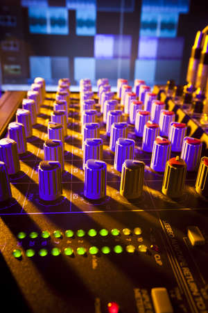 Close-up of audio mixing desk with background computer screen  Selective focus on foreground controls