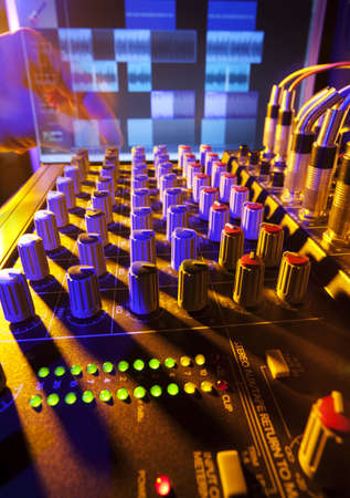 Close-up of an audio mixing desk with background computer screen  Motion blurred hand on distant controls  Selective focus on mixer controls Stock Photo