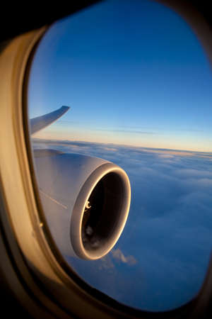 airplane window: Passenger view through the window of a jet plane showing sky, clouds, jet engine and wing  Stock Photo