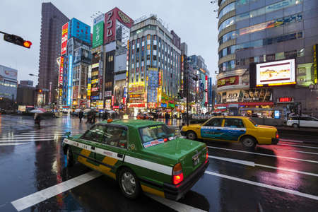 colourfully: Tokyo, Japan - March 2, 2012  On a rainy evening, two Tokyo taxis wait at a road junction on Yasukuni Dori in Shinjuku, with colourfully lit buildings in the background