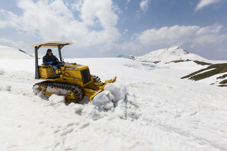 accessed: Murodo, Japan - May 16, 2012  A man uses a bulldozer to clear snow from a footpath on Mt  Tateyama in the Japanese Northern Alps  The walking path is accessed on the Tateyama Kurobe Alpine Route, a popular mountain trail traversing from Toyama to Omachi b