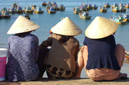 MUI NE, VIETNAM - FEB 2005   Three women in conical hats wait at the harbourside for the morning catch, Mui Ne, Vietnam on 10th February 2005 Stock Photo