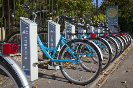 electronically: Bath, United Kingdom - October 2, 2011: A row of Bike in Bath rental cycles parked at the automatic docking station in Sydney Place. The bikes are secured to racks with electronically operated locks and can be rented on a self service basis using a pass