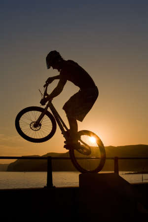 bicycle rider silhouetted at sunset, hops off a concrete walkway on the harbour wall at West Bay in Dorset