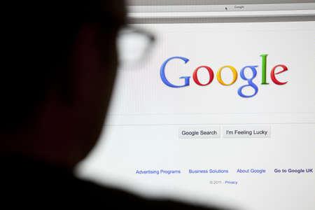 constat: Bath, Royaume-Uni - 4 mai 2011: Gros plan sur la page d'accueil de recherche Google.com affich�e sur un �cran d'ordinateur LCD avec la silhouette de la t�te d'un homme hors foyer au premier plan. �ditoriale