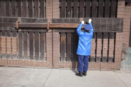Kyoto, Jap�n - 19 de marzo de 2012: Un guardia de seguridad en un uniforme azul bloquea la gran puerta de entrada de madera de Nijo castle en Kyoto, Jap�n. Foto de archivo - 18614605