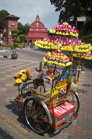 Melaka, Malaysia - November, 25 2004: Colourful Trishaw decorated with flowers and red painted Christ Church in the background
