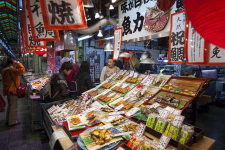 pesce cotto: Kyoto, Giappone - 23 marzo: Il personale ed i clienti in una bancarella vende pesce cotto nel mercato alimentare Nishiki a Kyoto Centrale il 23 marzo 2012. Editoriali