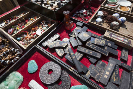 Close-up of a selection of antiquities for sale at an outdoor flea market in Kyoto, Japan