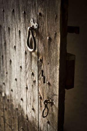 ajar: Old wooden door left ajar. Wood plank construction with metal studs, handle and catch.