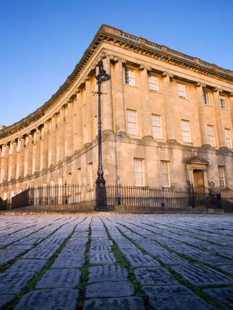 british culture: Royal Crescent in Bath, England with foreground cobbled street.