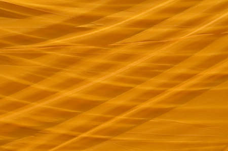 cross hatch: close up of a large sheet of orange material covering a reclining buddha in Thailand.