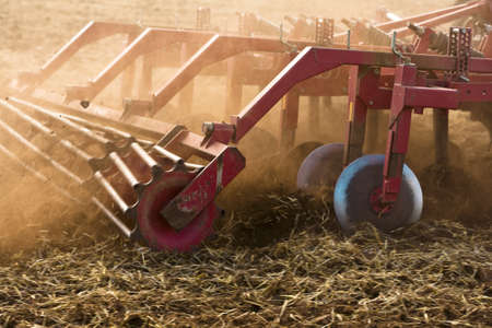 Tractor pulled plough cultivating a field. Motion blur on rotating parts and field. Stock Photo - 18633825
