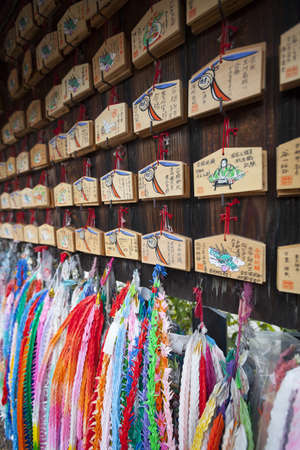 worshipers: Kyoto, Japan - March 18, 2012: Close-up of prayer tablets and chains of paper origami cranes hanging at a Shinto shrine. The small wooden tablets, called Ema, are left by worshipers with wishes written on them for the gods and spirits to receive. The stri Editorial