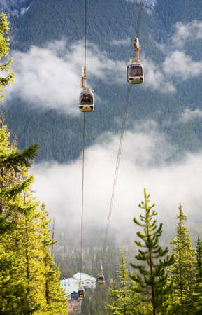 cable cars of Banff Gondola viewed from the trail halfway up Sulphur mountain, Banff National Park, Banff, Alberta, Canada.