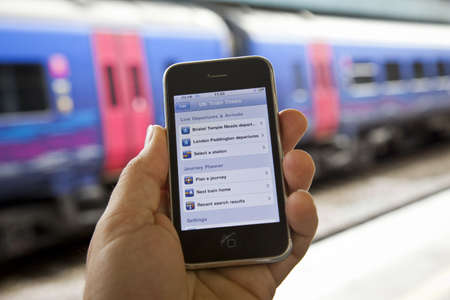 Bristol, United Kingdom - October 4, 2011: A male hand holding up an Apple iPhone 3Gs at Bristol Temple Meads station with train carriages out of focus in the background. The smart phone is running the UK train time app, which is used to plan trips and re