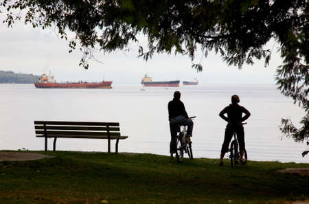 two cyclists in Stanley park take a break and admire the ships across English Bay in Vancouver, British Columbia, Canada. Stock Photo