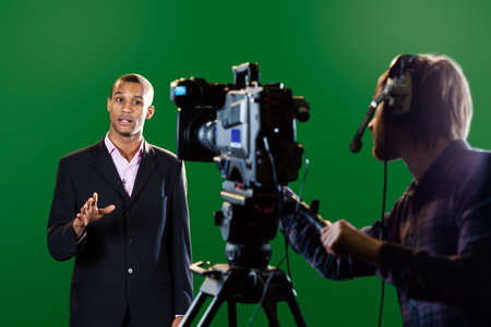 presenting: Television presenter in a studio  Foreground television camera and camera operator