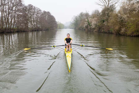 sculling: One man in a single scull rowing boat on the river Avon in Bath, UK