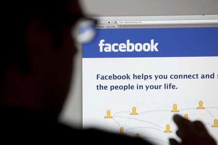 Bath, United Kingdom - May 4, 2011: Close-up of the Facebook homepage displayed on a LCD computer screen with silhouette of a man Stock Photo - 19415931