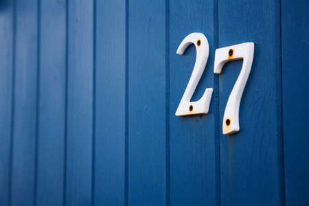 beach hut: Close up of the number twenty seven on the side of a blue beach hut.
