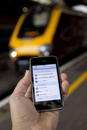 Bristol, United Kingdom - October 4, 2011: A male hand holding up an Apple iPhone 3Gs at Bristol Temple Meads station with a train out of focus in the background. The smart phone is running the UK train time app, which is used to plan trips and retrieve l