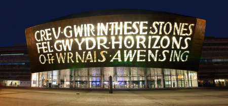 Nighttime exterior view of the Welsh Millenium Centre in Cardiff Bay, Cardiff, UK