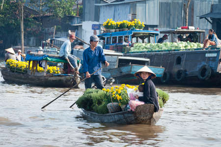CAN THO, VIETNAM - FEBRUARY 1 : Man and woman holding a baby on a wooden boat laden with plants and flowers at the floating market in Can Tho on the Mekong Delta, Vietnam on 1st February 2005.