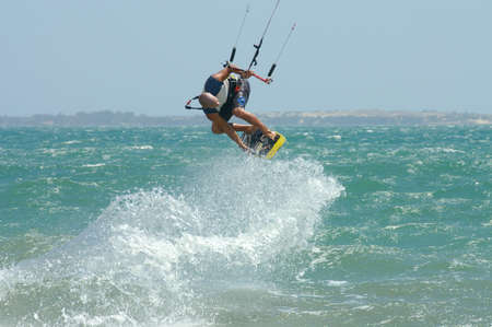 Mui Ne, Vietnam - February, 11 2005: A man performs a kitesurf trick, grabbing his board mid-air with one hand. The kite pulls him backwards at speed above the water, causing a large trail of sea spray.