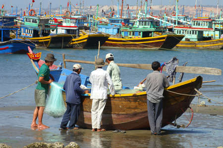 adult vietnam: Mui Ne, Vietnam - February, 10 2005: Group of men on the shore gather around a small wooden boat and prepare fishing materials. Mui Ne has a busy fishing harbour and many colourful fishing trawlers can be seen in the background.